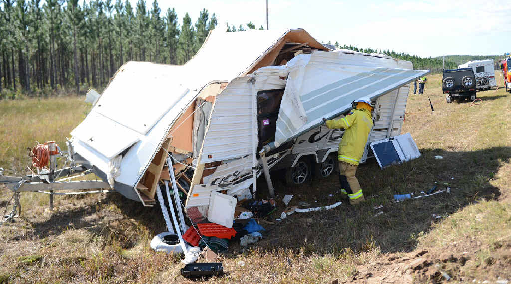 A Tin Can Bay fire and rescue officer checks out the damage done to a caravan that rolled on Tin Can Bay Rd yesterday.