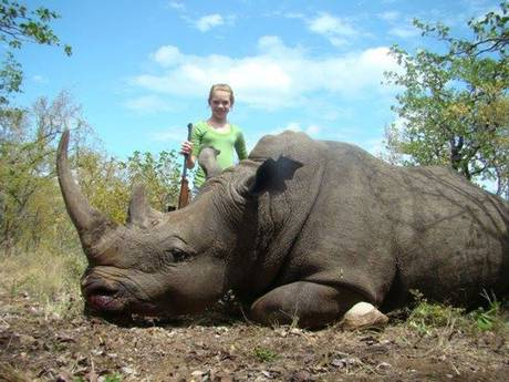 Kendall Jones poses beside an endangered rhinoceros, infuriating animal rights activists