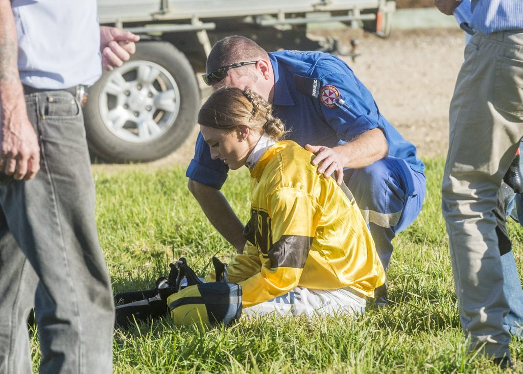 Jockey Cassandra Schmidt treated on course after a fall in race 6 on Westlawn day brought down three jockeys. Photo: Adam Hourigan / The Daily Examiner