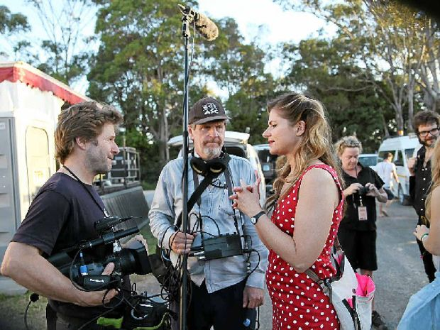 ROCKING TIME: Scene from the filming of RocKwiz Backstage at Bluesfest with host Julia Zemiro. Local sound recordist Darmin Cameron (centre) worked on set.