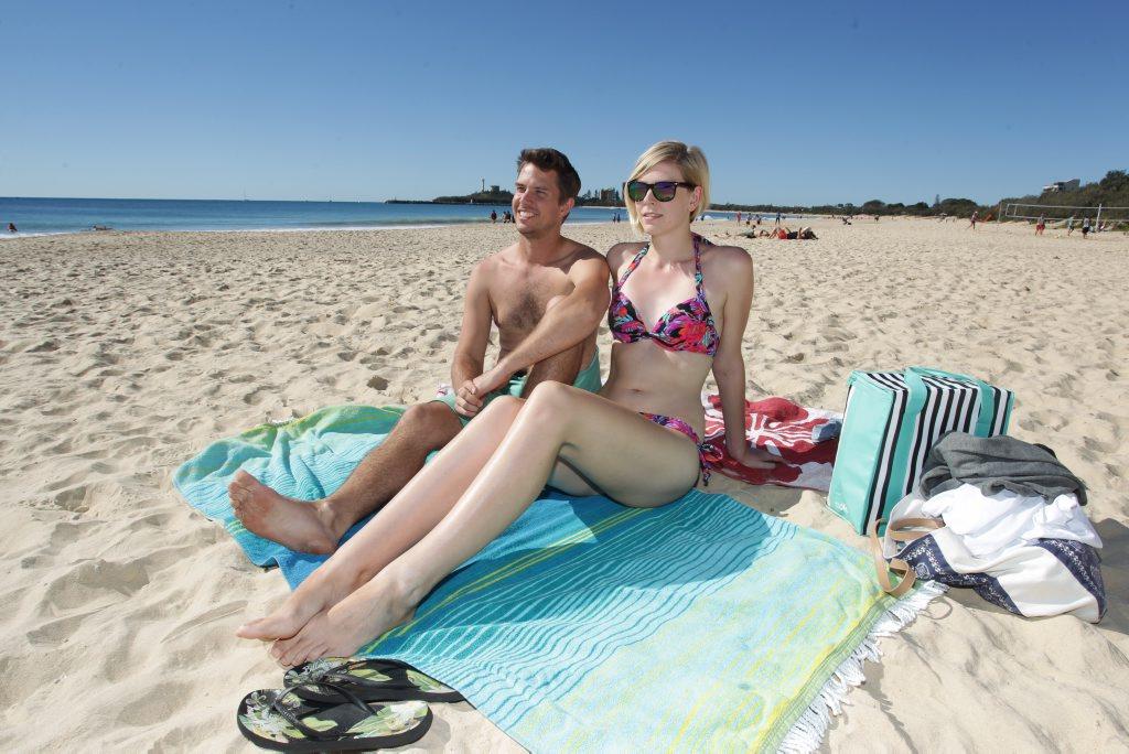 Matt Coutts and Louise Dann soak up some winter sun at Mooloolaba Beach. Photo: Brett Wortman / Sunshine Coast Daily