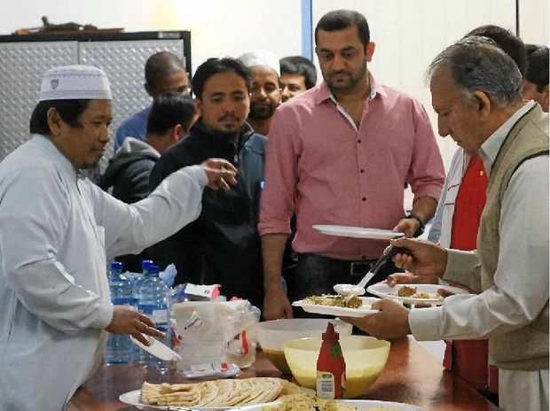 """Islamic Society of Gladstone president Dzulkamal Ahmad passes out plates for """"iftar"""", a big meal taken after sunset."""
