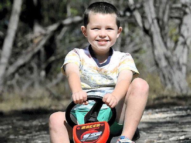 FULL OF LIFE: Brett Jones riding his go-kart down the driveway of the family home in Maroondan.