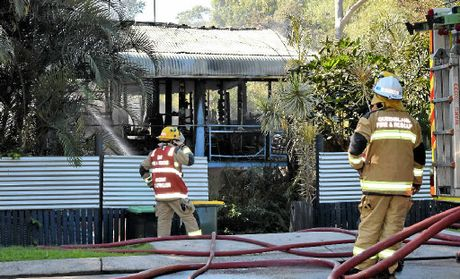 GONE IN MINUTES: Firefighters hose down the charred home in Toolga St, Mt Coolum. A candle is believed to have set fire to a curtain in a bedroom.