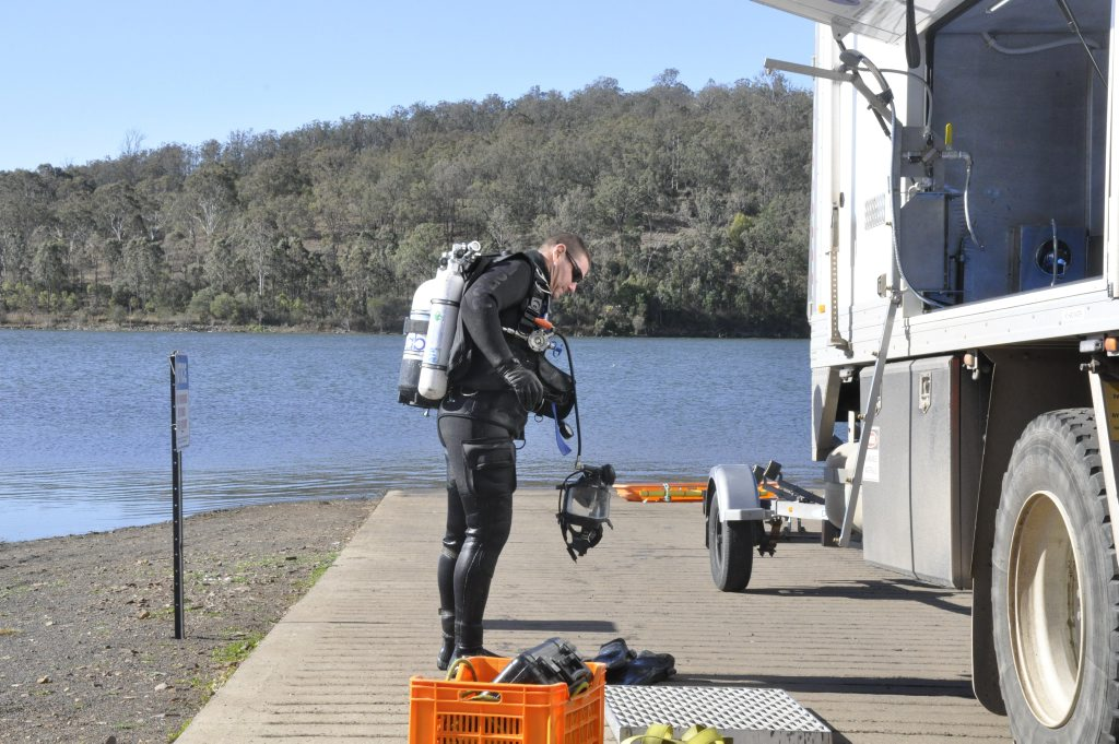 Police divers return to shore at Cooby Dam after retrieving the body of drowning victim John Ryan. Photo: Stuart Cumming / The Chronicle