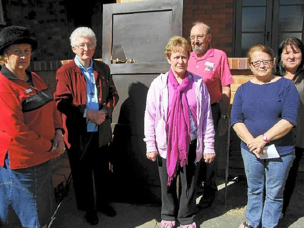 ROBBED: Parishioners Lindsay McMillan, Merril Ruback, Diane Draper, Herb St Pierre, Kerry Yates and Lea-anne Williams with the door that was smashed.