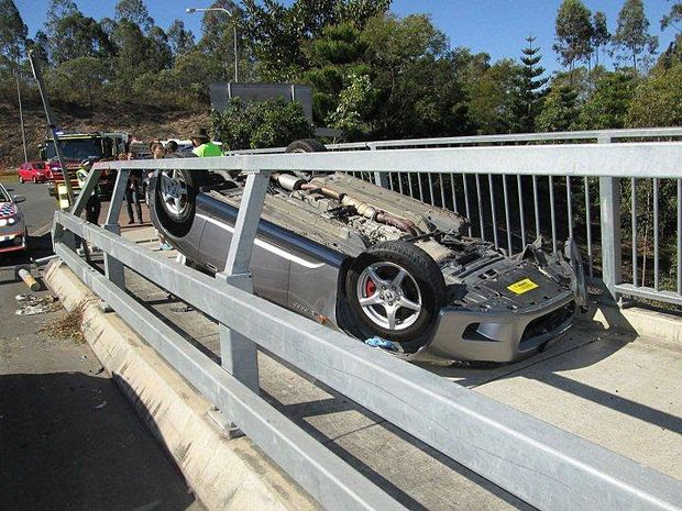 LUCKY ESCAPE: The car came to rest in an unlikely position on a bridge in Springfield Central.
