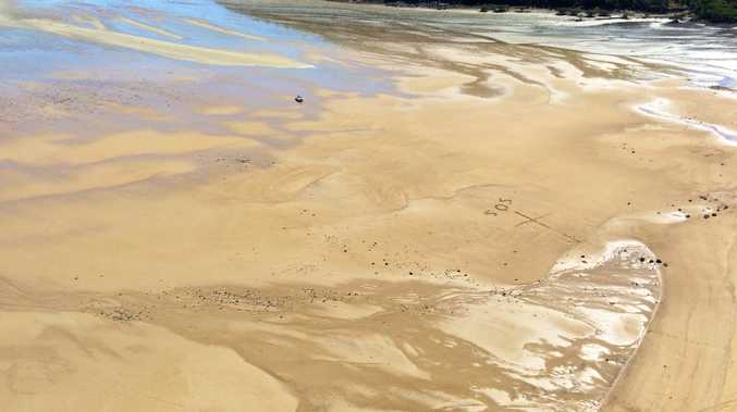 SOS written in sand help RACQ CQ REscue helicopter locate woman who fell from tree.