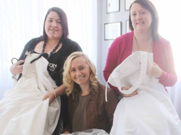 MADE WITH LOVE: From left, Tania Raine, Jacqui Pitts and Lisa Briggs holding their own wedding gowns, are the Rockhampton coordinators for the Angel Gown program, which makes dresses from wedding gowns that are given to babies who have sadly passed away.