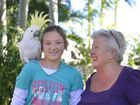 Tegan Hallcroft, 12, with Lorraine de Roode and their talkative cockatoo Darling. Photo Brenda Strong / The Observer