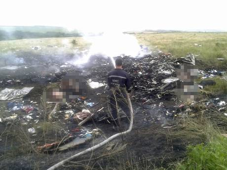 A man works at putting out a fire at the site of the plane crash