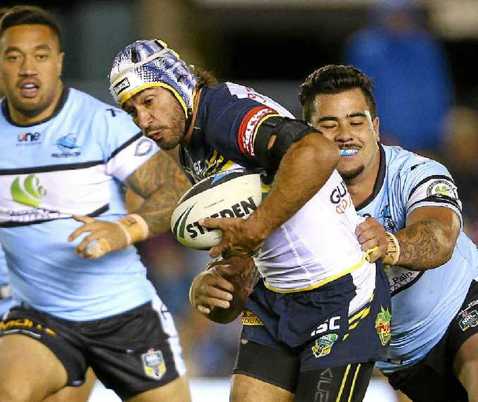 ON THE RUN: Johnathan Thurston of the Cowboys makes a break from the grasp of Andrew Fifita of the Sharks at Remondis Stadium in Sydney last night.