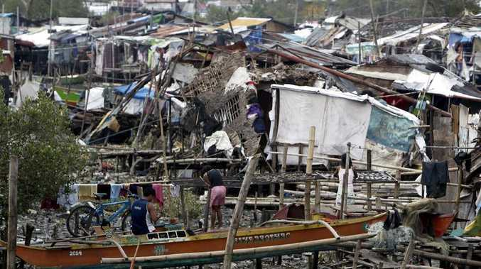 Filipinos clear debris outside their damaged houses after strong winds and rain brought by Typhoon Rammasun at a fishing village in Paranaque city, South of Manila, Philippines, 19 July 2014.