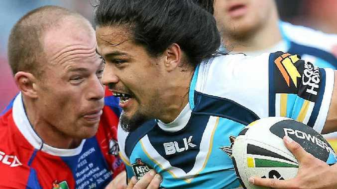 Titan Kevin Gordon tries to break the tackle of Knight Beau Scott at Hunter Stadium yesterday.