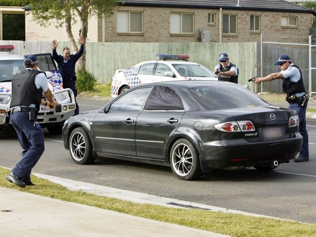 YOU'RE SURROUNDED: Police pounce on the vehicle of a suspected armed offender in Redbank Plains.
