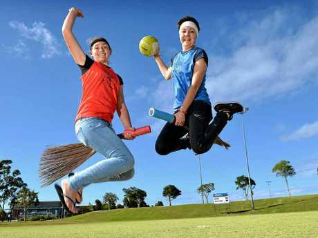 WIZARDS WIND UP: Uni students Chloe Grabs and Abbey Crook practise for the Quidditch battle.