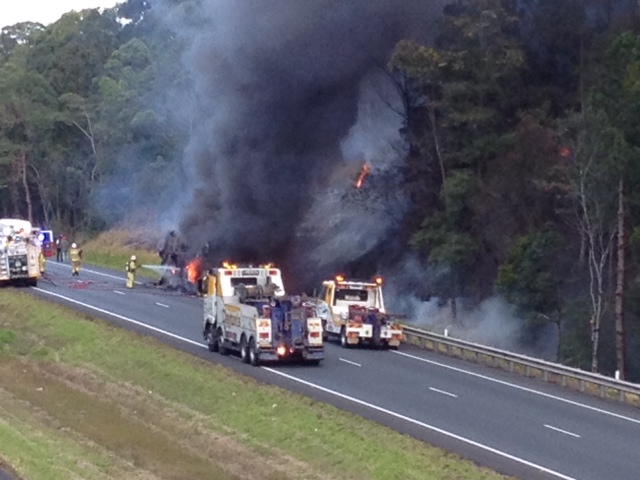 Firefighters at the scene of a school bus fire on the Bruce Highway near Ilkley Road.