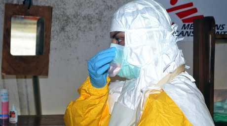 A member of Doctors Without Borders (MSF) puts on protective gear at the isolation ward of the Donka Hospital, on July 23, 2014 in Conakry, Guinea
