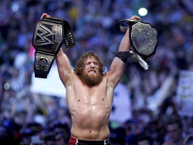 This April 6, 2014 photo provided by the WWE shows Daniel Bryan celebrating after winning the main event during Wrestlemania XXX at the Mercedes-Benz Super Dome in New Orleans. Police say the former WWE champion, Bryan chased two burglary suspects he saw exiting his Phoenix home this week and subdued one until officers arrived.