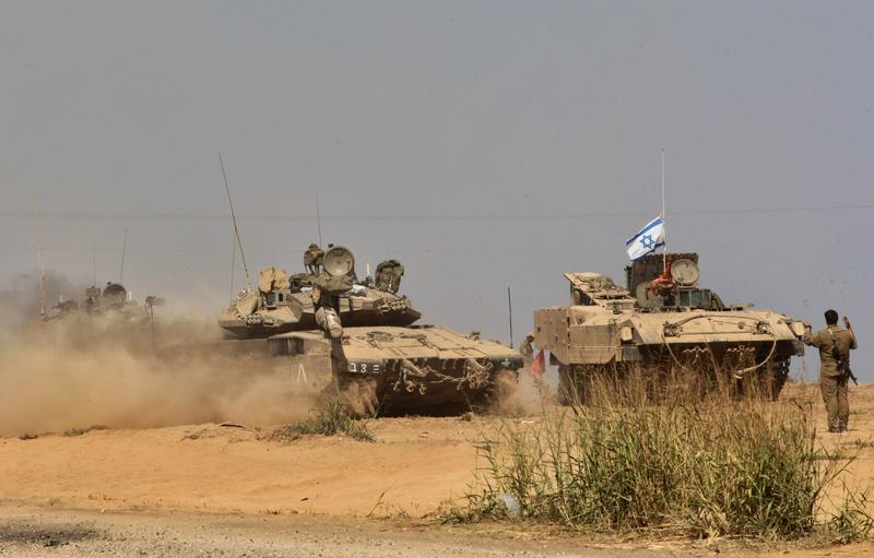 Israeli Merkava tanks take position at an army deployment along the Israeli border with the Hamas-controlled Gaza Strip on July 27, 2014. The Islamist Hamas movement belatedly accepted diplomatic calls for an extension of a humanitarian ceasefire in Gaza shortly after Israel said it was resuming its devastating military assault.