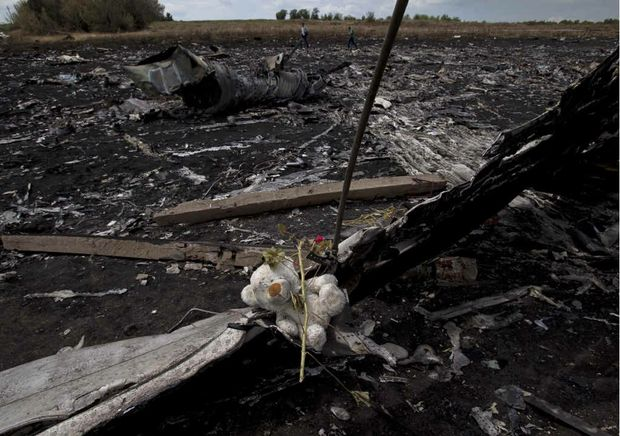 A toy bear is placed on charred plane fuselage parts, as people walk through the crash site of Malaysia Airlines Flight 17 near the village of Hrabove, eastern Ukraine.