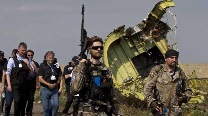 Pro-Russian rebels, with guns, pass plane wreckage.