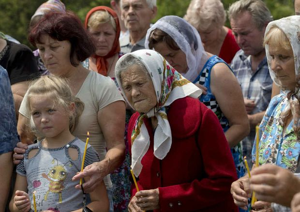 A women cries during a religious service held by villagers in memory of the victims at the crash site of Malaysia Airlines Flight 17, near the village of Hrabove, eastern Ukraine.