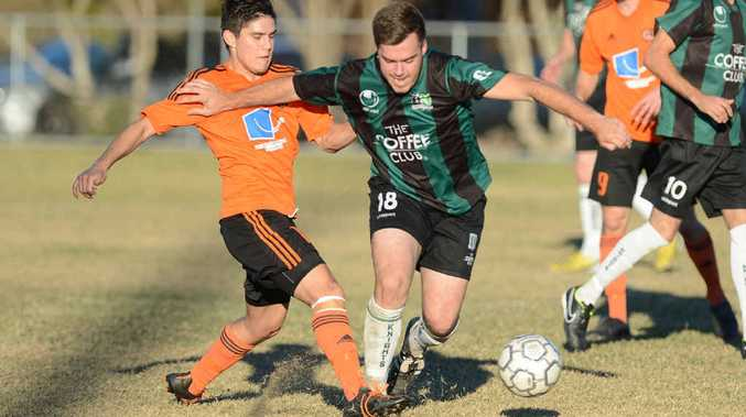 MIDFIELD BATTLE: Ipswich Knights player Dale Robinson works hard to outrun an Easts tackler during yesterday's Brisbane Premier League match at Bundamba. Easts won 3-1.