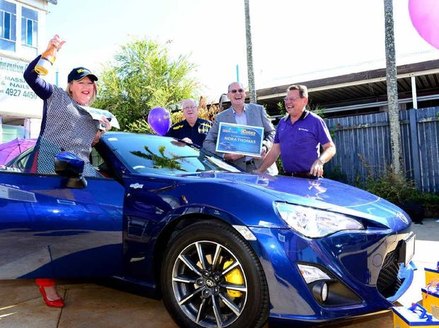 HITTING THE JACKPOT: Nora Thomas gets ready to drive her new Toyota 86 GT sports car away from Battery World, pictured with Mick McAtee and Allan Woodford from Century Yuasa Batteries Pty Ltd and owner of Battery World in Rockhampton Skip Wren.