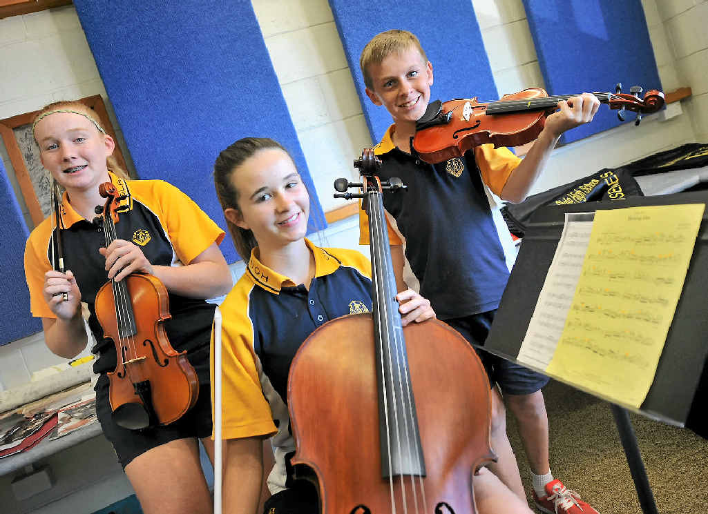 CLEVER KIDS: Gladstone State High School students (left) Emma, 14, Hayley, 14, and Josh, 12, get some lessons from the state's best musicians yesterday.