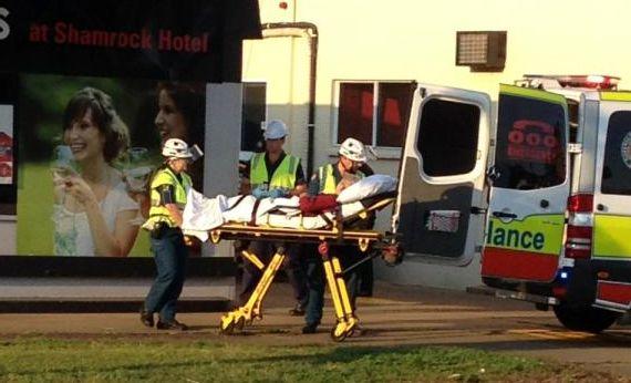 A man is wheeled into an ambulance after a crash at the Shamrock Hotel's drive-thru bottle shop.
