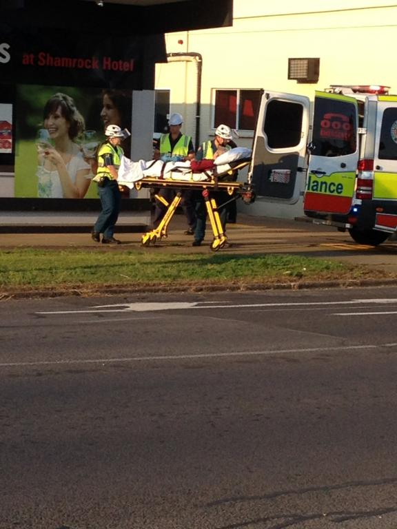 A man is wheeled into an ambulance after a crash at the Shamrock Hotel's drive-thru bottle shop.