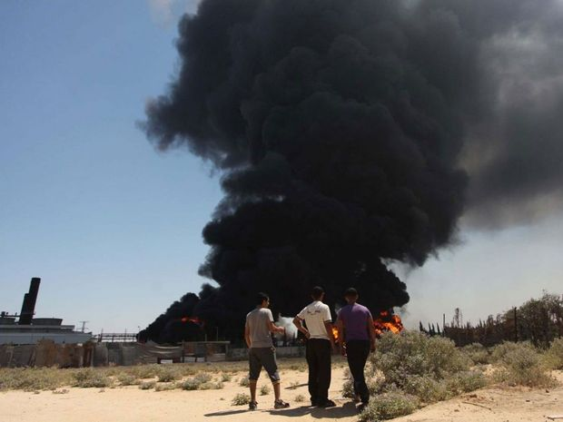 Thick black smoke rises from the burning fuel tank of a power plant in Gaza region, after it was struck by two tank shells
