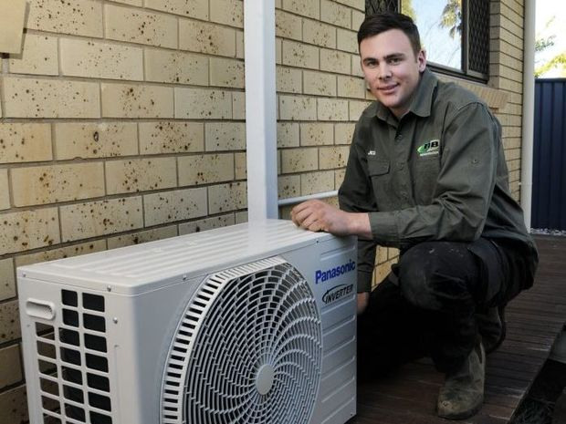 NB Refrigeration apprentice refrigeration mechanic Jed Ryan installs one of three new split system air-conditioners at the home of Det. Sgt Darren Lees.
