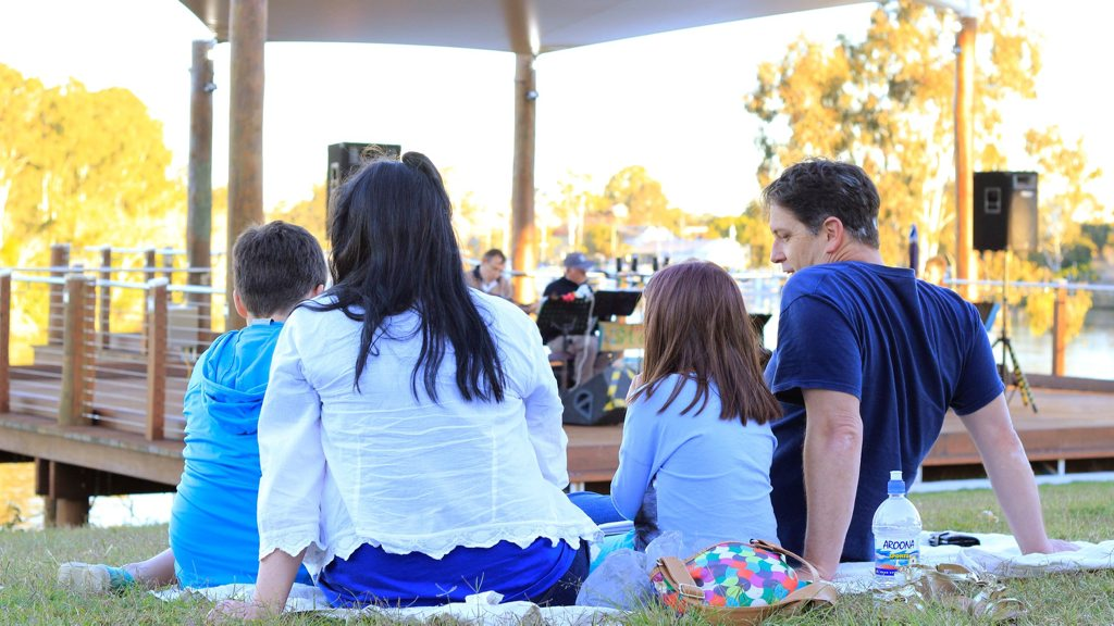 A family enjoys the band playing at Sunday Riverside on the lawn of the Brolga Theatre in Maryborough.