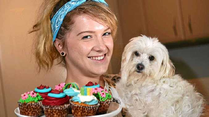 BAKED WITH LOVE: Jessica Putt with her rescue dog Mackie and examples of the treats in store on Cupcake Day.