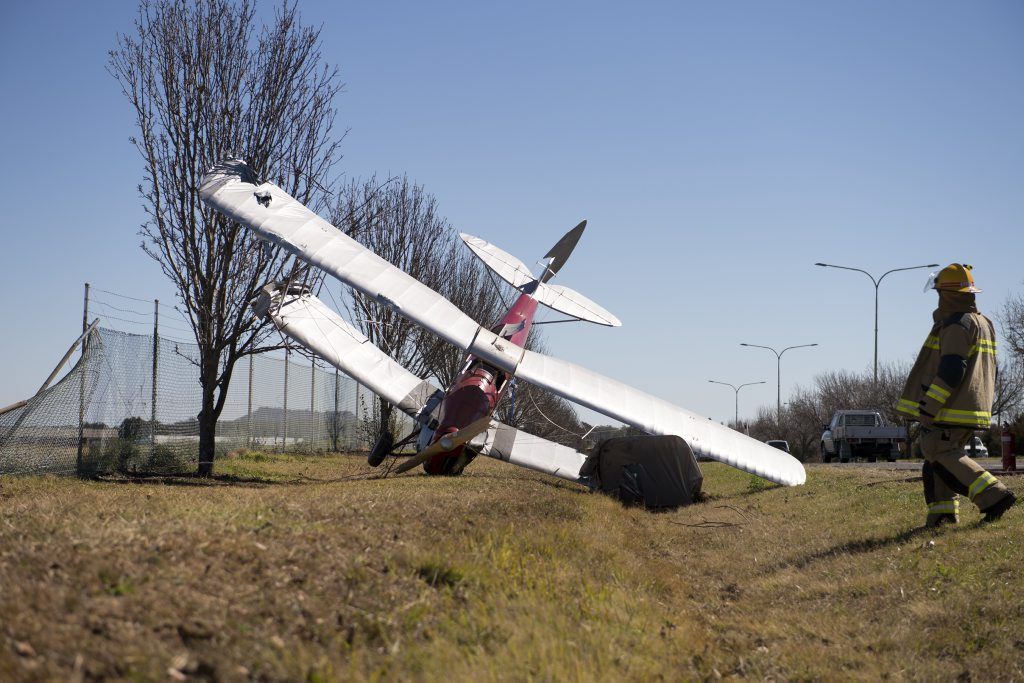 The wreckage of Al McVinish's De Havilland Tiger Moth lays beside the Warrego Hwy after crashing at Toowoomba Airport on Saturday