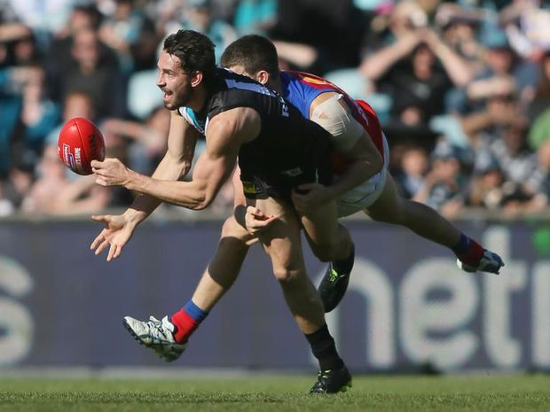 John Butcher of Port Adelaide looks to hand ball before being tackled by Jack Crisp of the Brisbane Lions during the Round 18 AFL match between the Port Adelaide Power and the Brisbane Lions at AAMI Stadium in Adelaide, Sunday, July 28, 2013.