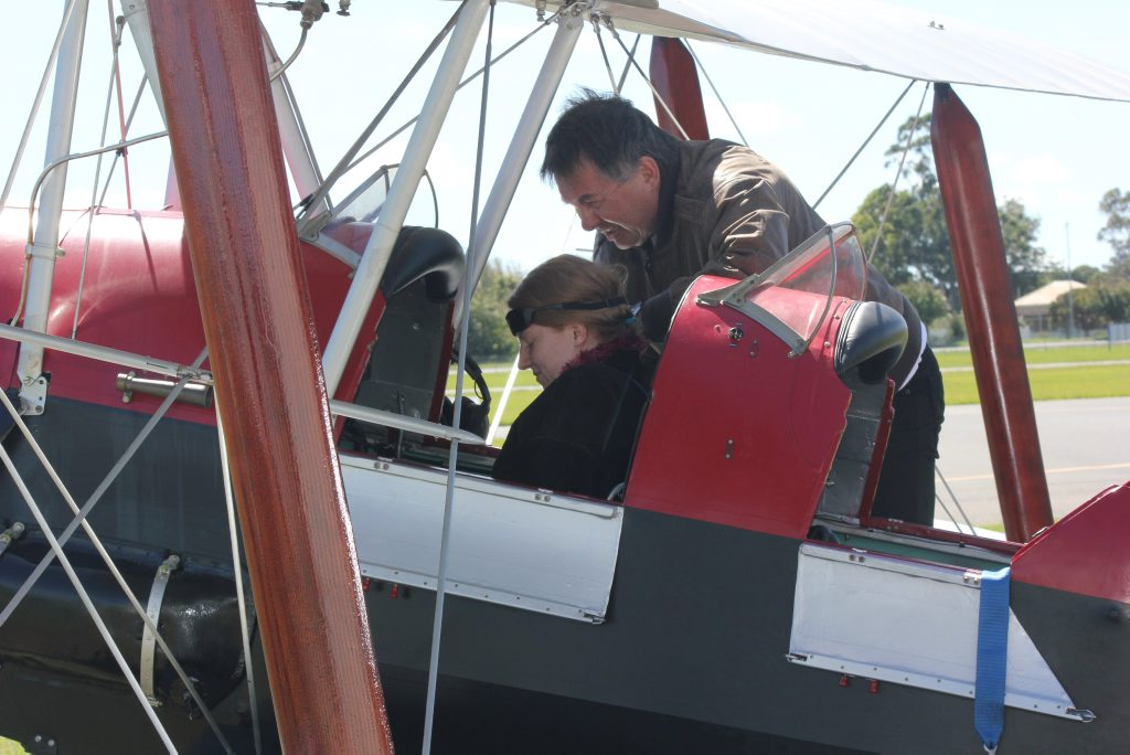 Former Solicitor-General Walter Sofronoff secures family friend Erin Miller into a 1939 De Havilland Tiger Moth at Toowoomba Airport earlier this year.