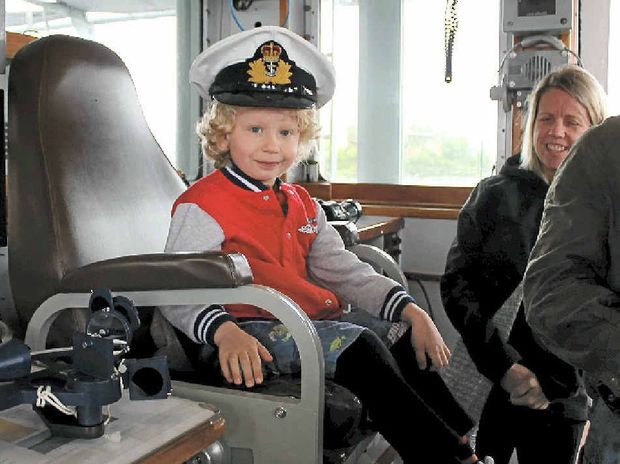 YOUNG SKIPPER: Owen Hooper, 4, from Ballina takes over the captain's seat on HMAS Labuan.