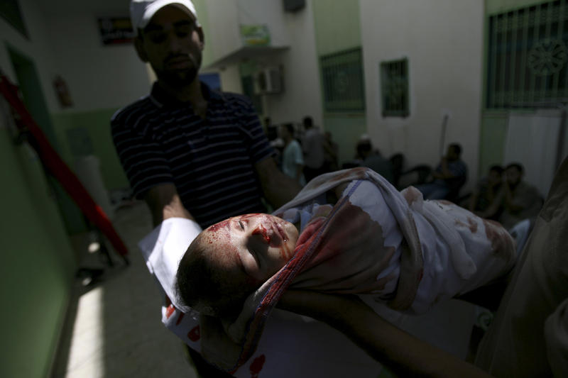 A paramedic carries a dead Palestinian child at a hospital, in Rafah, southern Gaza Strip, Saturday, Aug. 2, 2014. Israel bombarded Rafah on Saturday as troops searched for an officer they believe was captured by Hamas in an ambush that shattered a humanitarian cease-fire and set the stage for a major escalation of the 26-day-old war.