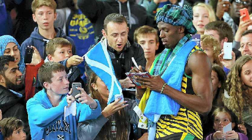 Usain Bolt signs autographs after winning gold in the men's 4x100 metres at Hampden Park wearing a tam o'shanter.