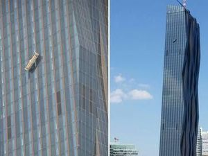 Window cleaners dangle on side of 250m building