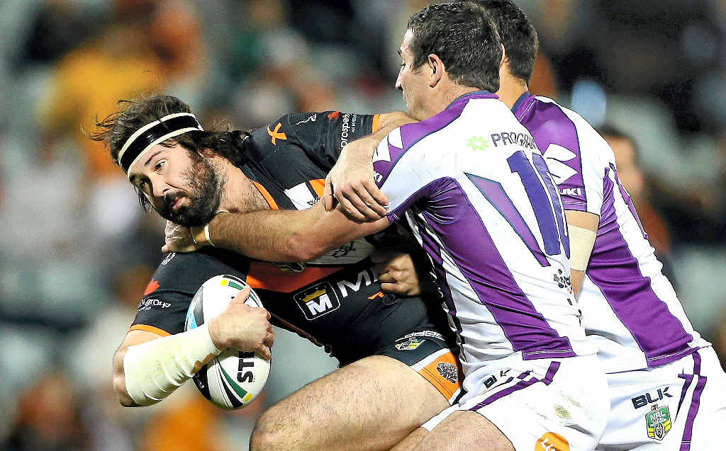 Aaron Woods of the Tigers is tackled by Bryan Norrie of the Storm at Campbelltown Sports Stadium in Sydney last night.