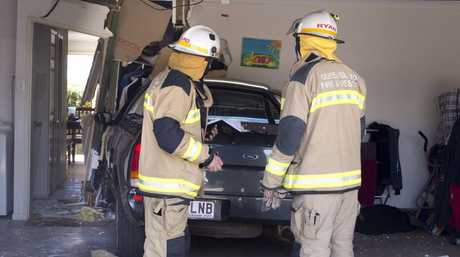 Firefighters inspect the damage caused when a ute crashed into the wall of a Newtown unit.