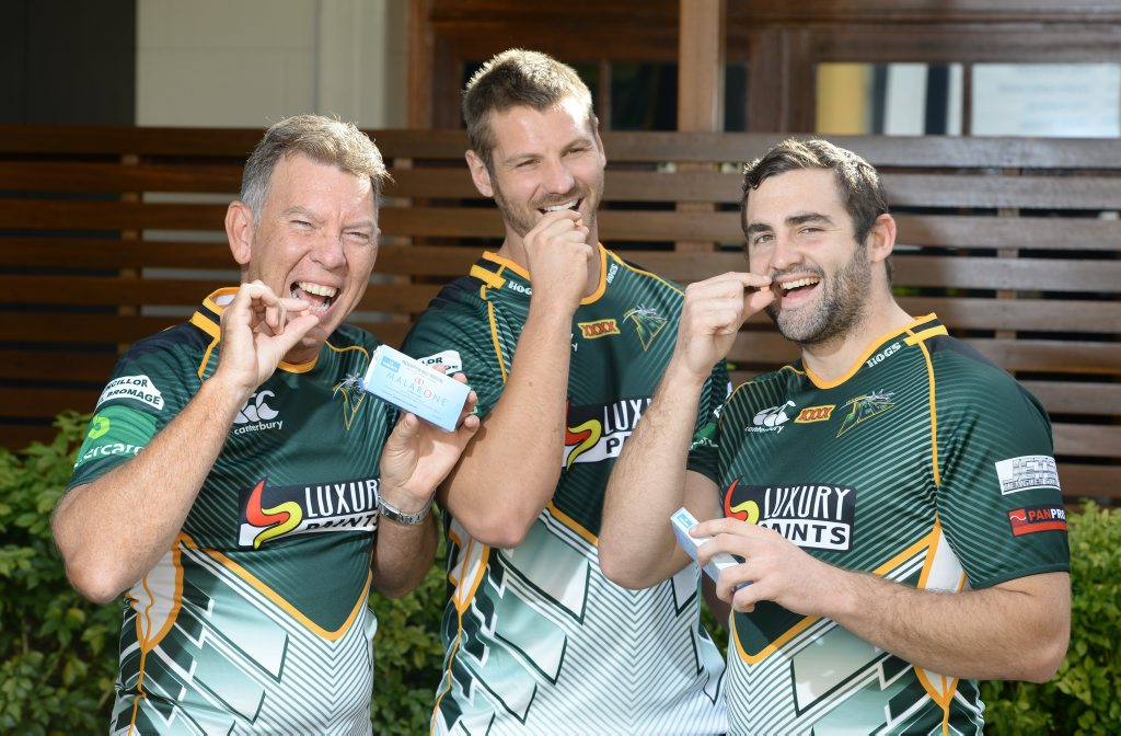 YUM: Ipswich Jets CEO Wayne Wendt and players Rob Worsley and Josh Seage take malaria tablets before their trip to PNG.