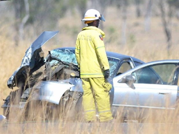 SERIOUS CRASH: Emergency services inspect the scene of an accident 20km south of Rockhampton on the Bruce Hwy. A silver sedan lies in a heap among the tall grass.