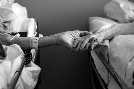 In this photo provided by their granddaughter, Melissa Sloan, Don Simpson, 90, and his wife Maxine, 87, hold hands from adjoining hospice beds in Sloan's home in Bakersfield, Calif.