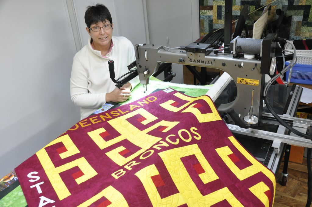 Irene Story with a quilt for a Broncos and Maroons supporter on HMAS Toowoomba.