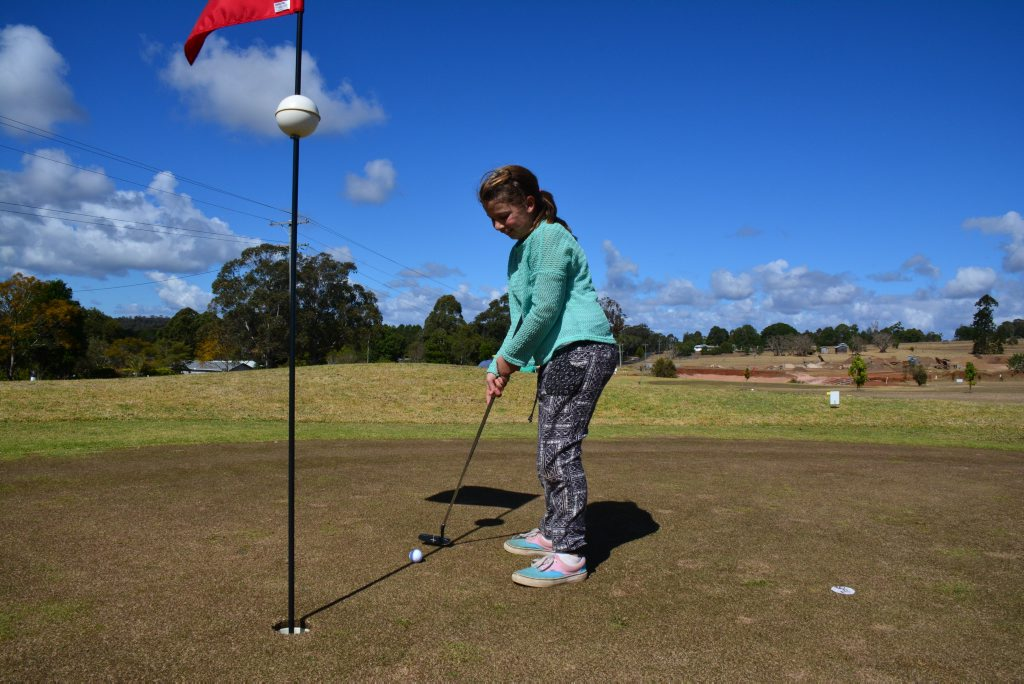 ON COURSE: Lillyana Beutel tries out her dad's putter. Photo Brandon Livesay/ South Burnett Times